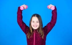 Para o corpo mais forte menina que exercita com dumbbell Exercícios do peso do novato Azul pequeno do peso da posse da criança imagem de stock royalty free