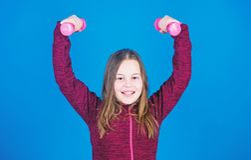 Para o corpo mais forte menina que exercita com dumbbell Exerc?cios do peso do novato Azul pequeno do peso da posse da crian?a fotos de stock royalty free