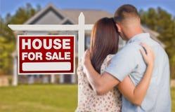 Para o sinal de Real Estate da venda, pares militares que olham a casa Imagens de Stock Royalty Free
