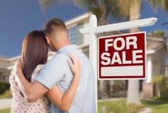 Para o sinal de Real Estate da venda, pares militares que olham a casa Imagens de Stock