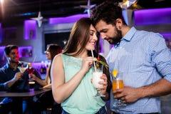 Para obejmuje each inny przy baru kontuarem podczas gdy mieć koktajl Fotografia Stock