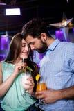 Para obejmuje each inny przy baru kontuarem podczas gdy mieć koktajl Zdjęcia Stock