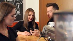 Para odpoczywa w sklepie z kawą, trzymają telefony, czekać na kawę zbiory wideo