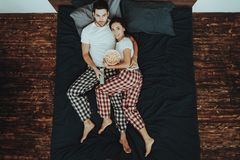 Para Ogląda wideo i Je popkorn na łóżku obraz stock