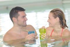 Para pije koktajl w pływackim basenie Zdjęcie Royalty Free