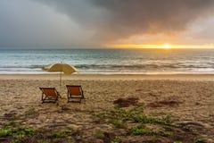 Para plażowi loungers i parasol na plaży przy zmierzchem lub wschodem słońca zdjęcie royalty free