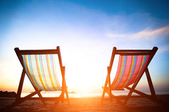 Para plażowi loungers na opustoszałym brzegowym morzu przy wschodem słońca Zdjęcia Royalty Free
