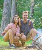 Para prażaka kiełbasy na kij natury tle Para w miłości cieszy się campingową lasową prażak kiełbasę przy ogniskiem zdjęcie royalty free