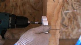 Para prender o dispositivo elétrico das tubulações plásticas a uma parede Mãos da pessoa em luvas de trabalho para torcer o paraf vídeos de arquivo