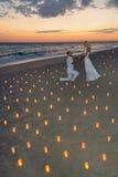 Para przy morze plażą w świeczkach przeciw zmierzchowi Zdjęcie Stock