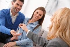 Para przy nieruchomości sprzedaży biurem z agentem daje kluczom Zdjęcie Royalty Free