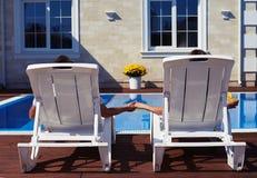 Para relaksuje przed nowożytnym domowym pobliskim basenem Obrazy Royalty Free