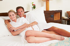 Para Relaksuje W pokoju hotelowym Jest ubranym kontusze Zdjęcia Stock