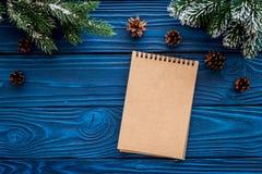 Para resumir el año Cuaderno cerca de la rama spruce en copyspace de madera azul de la maqueta de la opinión superior del fondo Fotografía de archivo
