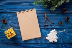 Para resumir el año Cuaderno cerca de los juguetes de la Navidad y decoración del Año Nuevo en maqueta de madera azul de la opini Fotografía de archivo