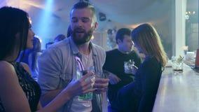 Para robi rozkazowi i komunikuje blisko baru odpierającego przeciw tłu firma przyjaciele w klubie zbiory wideo
