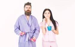 Para, rodzina oferuje alternatywnego energetycznego źródło Dobiera się w miłości w piżamie, bathrobe stojak odizolowywający na bi zdjęcie royalty free