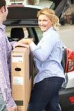 Para Rozładowywa Nową telewizję Od Samochodowego bagażnika zdjęcie stock