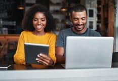 Para ruchliwie w używać urządzenia elektroniczne przy café zdjęcie royalty free