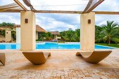 Para słońc loungers na krawędzi basenu, otaczająca pa Zdjęcie Stock