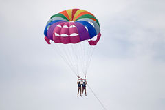 Para-sailing. Two people para-sailing by colorful parachute Royalty Free Stock Photo
