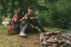 Para siedzi blisko obozu pożarniczego, pić herbaciany i mówić opowieści namiot i suv na tle fotografia stock