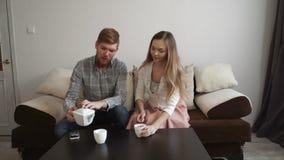 Para siedzi na leżanki kanapie, ogląda tv, i w domu, napój herbata od białego herbata setu zdjęcie wideo