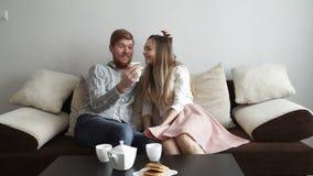 Para siedzi na leżanki kanapy spojrzeniu w domu w smartphone uśmiech i, napój herbata od białego herbata setu i zbiory wideo