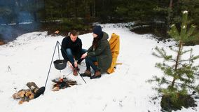 Para siedzi ogniskiem w zima lesie w wygodnych leżankach _ Szczęśliwy zimy pojęcie zbiory