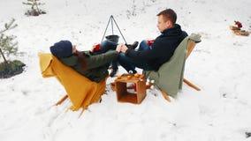 Para siedzi ogniskiem w zima lesie w wygodnych leżankach _ Szczęśliwy zimy pojęcie zbiory wideo