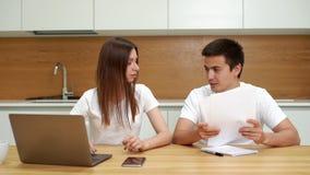 Para siedzi przy kuchennym stołem, używa laptop, i brać opieka rachunek za usługę komunalną zbiory
