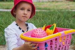 Para sostener a disposición una cesta con los juguetes de la arena Imagenes de archivo