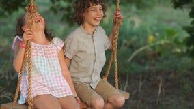 Para szczęśliwi dzieciaki ściska i huśta się na drewnianej huśtawce przy złotym zmierzchem Brat obejmuje małej siostry na huśtawc zbiory