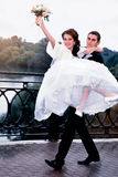 para szczęśliwy ślub Fornal niesie jego pięknej panny młodej na rękach Fotografia Stock
