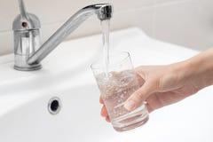 Para tirar a água em um vidro Foto de Stock