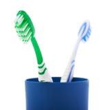 Para toothbrushes w błękitnej plastikowej filiżance odizolowywającej nad białym tłem Zdjęcie Stock