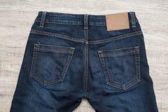 Para trás da calças de ganga no fundo de madeira com etiqueta de couro marrom imagem de stock royalty free