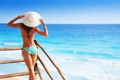Para trás da menina bonita no cais que guarda o chapéu branco Fotografia de Stock Royalty Free