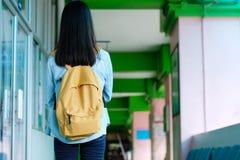 Para trás da menina do estudante que guarda livros e para levar o saco de escola ao andar no fundo do terreno da escola, educação foto de stock