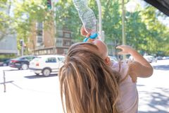 Para trás da menina que bebe da garrafa plástica na rua Imagem de Stock