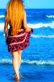 Para trás da mulher 'sexy' loura que anda no mar Fotografia de Stock