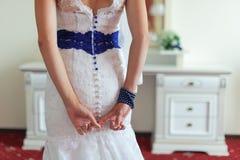 Para trás da noiva, das mãos e de um vestido com botões azuis Imagens de Stock Royalty Free