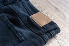 Para trás das calças de brim no fundo de madeira com etiqueta de couro fotografia de stock