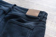 Para trás das calças de brim no fundo de madeira com etiqueta de couro foto de stock royalty free