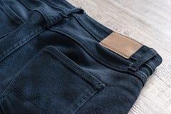 Para trás das calças de brim no fundo de madeira com etiqueta de couro fotografia de stock royalty free