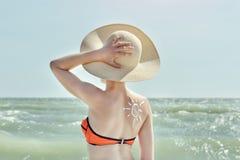 Para trás de uma menina com um sol de creme pintado imagens de stock