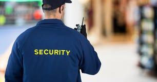 Para trás do agente de segurança com o Walkietalkie contra o centro de compra obscuro fotografia de stock royalty free
