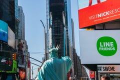 Para trás do caráter da estátua da liberdade com as construções vistas no Times Square no fundo foto de stock royalty free