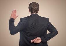 Para trás do homem de negócio com a mão ascendente e os dedos cruzou-se contra o fundo de creme Fotografia de Stock