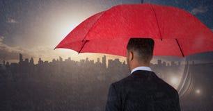Para trás do homem de negócio com o guarda-chuva contra a skyline com por do sol e chuva Imagem de Stock